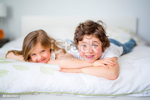 istock Brother And Sister Relaxing Together In Bed 853920522