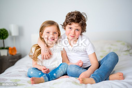 istock Brother And Sister Relaxing Together In Bed 853920574