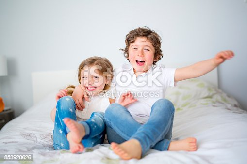 istock Brother And Sister Relaxing Together In Bed 853920626