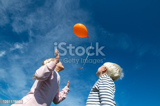 Low angle view of blonde brother and sister releasing an orange balloon into the sky.