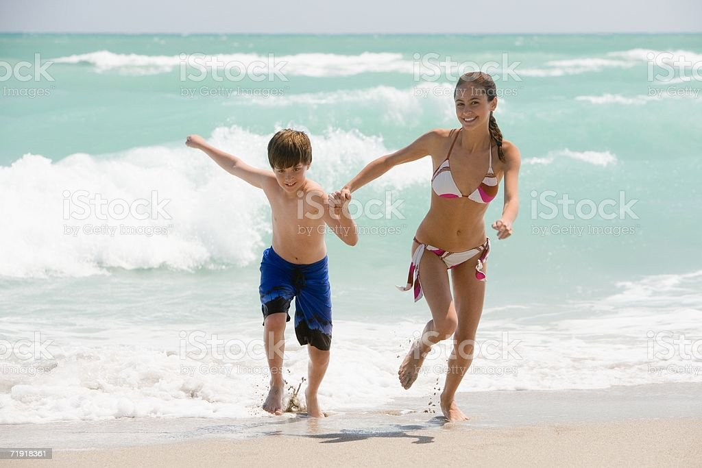 Brother and sister running on the beach stock photo