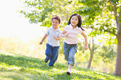 Brother and sister running outdoors smiling in summer during the day