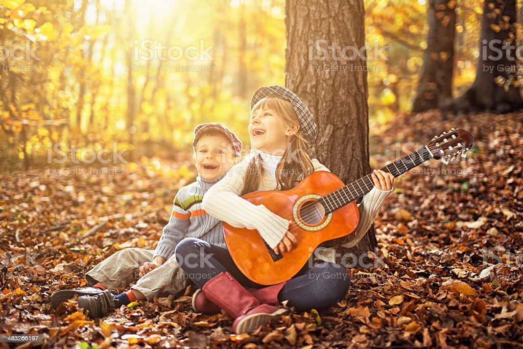 Brother and sister singing together in autumn forest. royalty-free stock photo