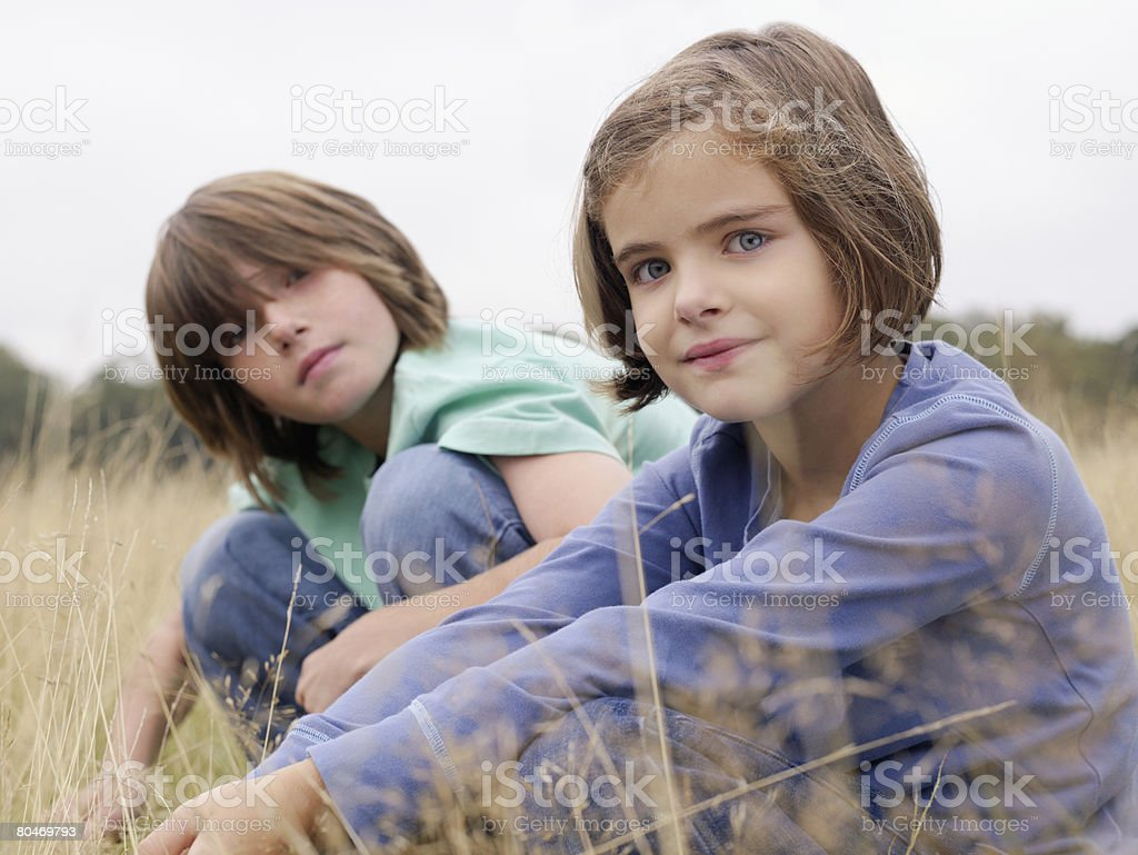 Brother and sister sitting in a field royalty-free stock photo