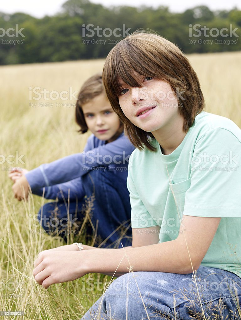 Brother and sister sitting in a field royalty-free 스톡 사진
