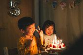 誕生日ケーキの前に座っている兄弟姉妹