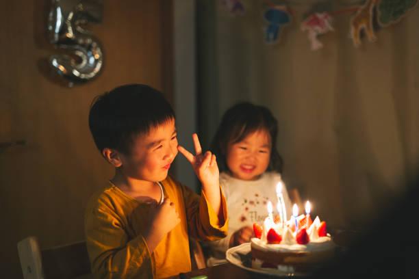Irmão e irmã sentados na frente do bolo de aniversário - foto de acervo