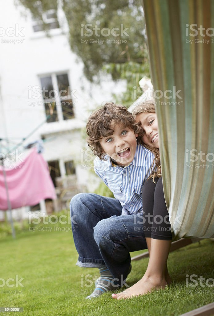 Brother and sister sitting in hammock royalty-free stock photo