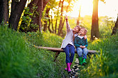 Little boy aged 5 and his elder sister aged 9 are sitting on the small bridge in the forest. They are enjoying beautiful nature and the sunset, smiling happily.