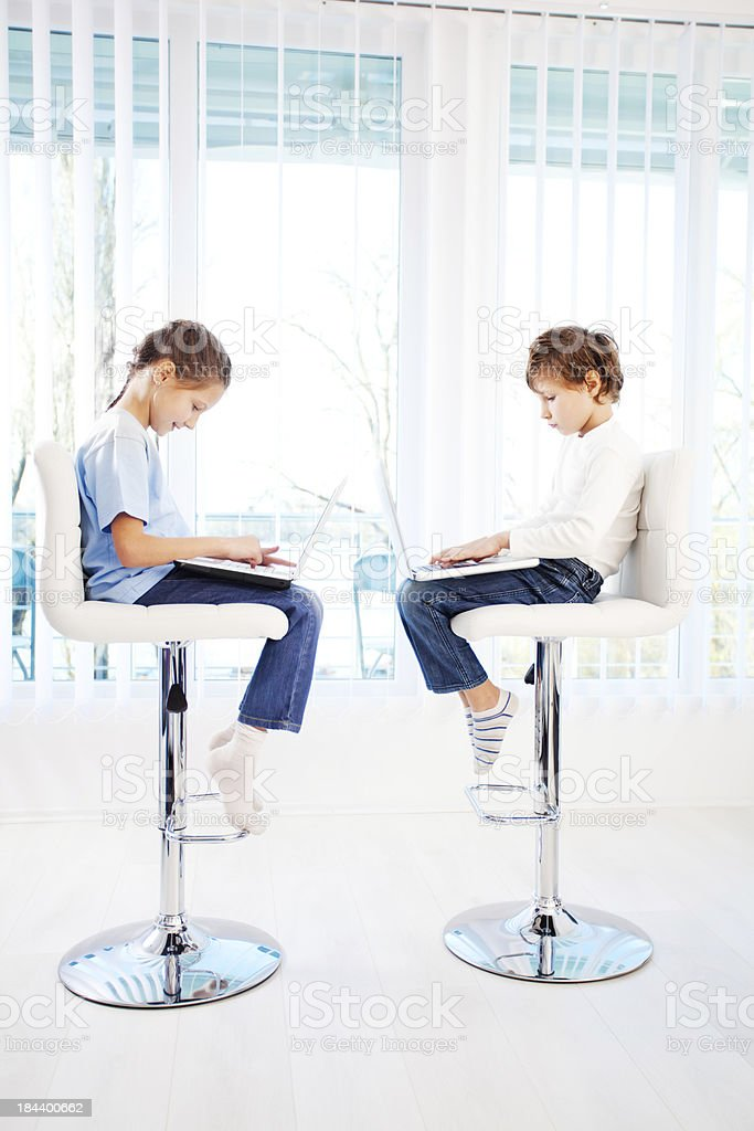 Brother and sister sitting on chairs, using laptops. royalty-free stock photo