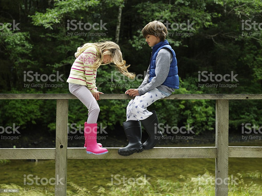 Brother and sister sitting on deck railing. royalty-free stock photo