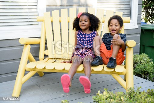 istock Brother and sister sitting on yellow bench, smiling 623700900