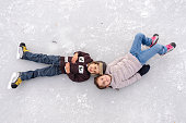 A brother and sister have fun on the ice as they learn to skate on a natural outdoor ice rink.