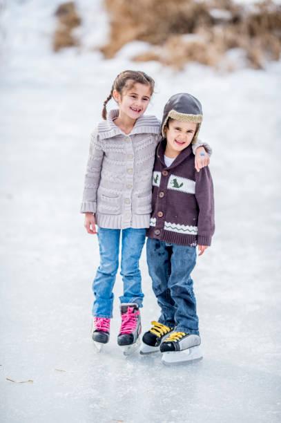 bruder und schwester, skaten - gute winterjacken stock-fotos und bilder