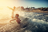 Children are having splashing fun in sea on summer sunset.  Children are aged 7 and 11.\nNikon D810