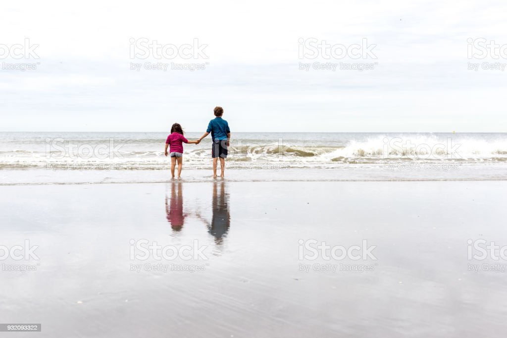 Brother and sister standing hand on the beach stock photo