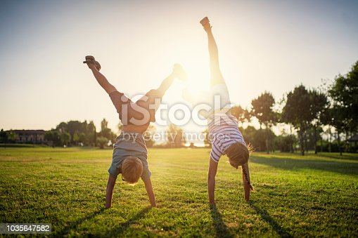 Little boy and his sister having fun on grass in park or garden. The kids are practicing standing on hands.  Sunny summer evening. Nikon D850