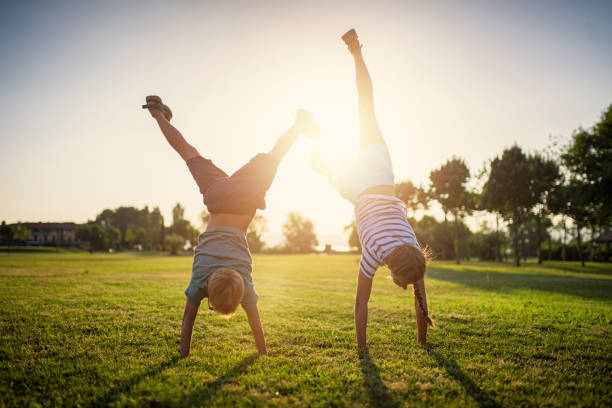 Brother and sister standing on hands on grass stock photo