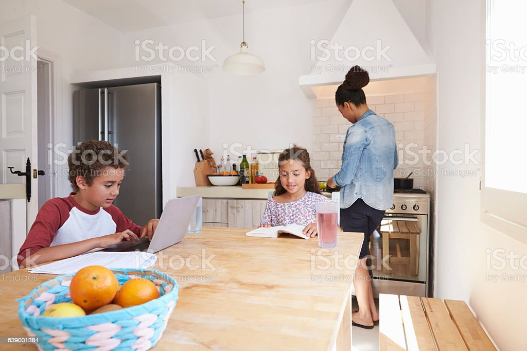 Brother and sister study in kitchen and mum cooks, close up stock photo