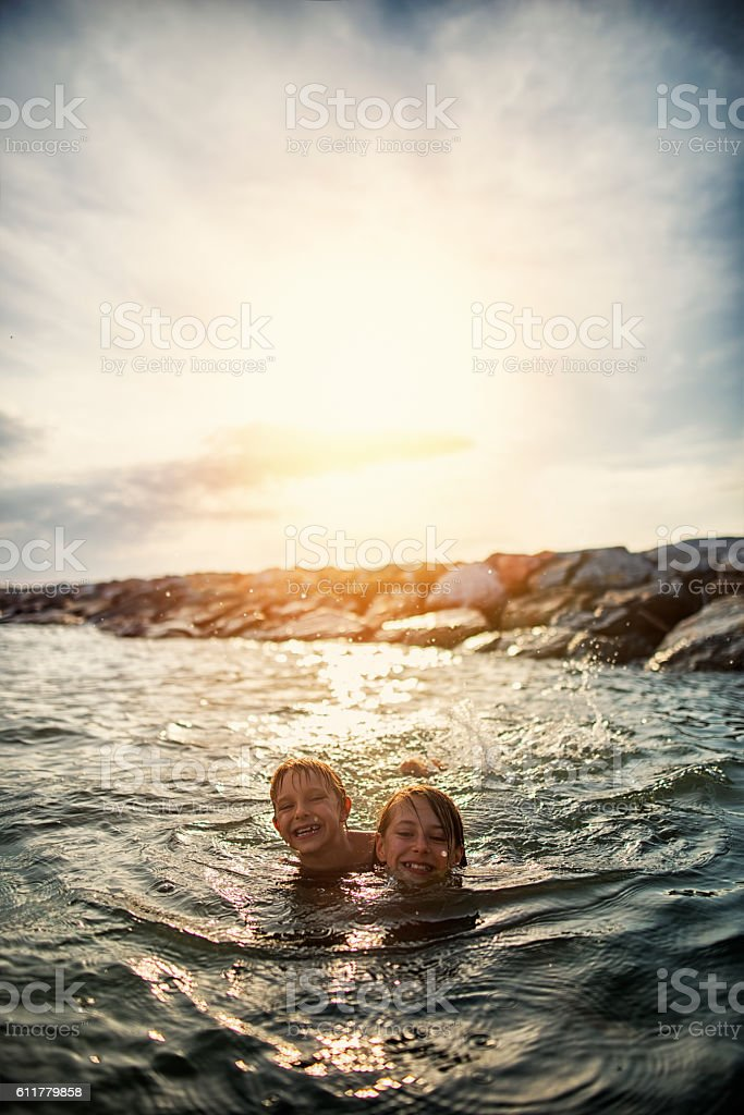 Brother and sister swimming in tuscan sea on sunset. stock photo