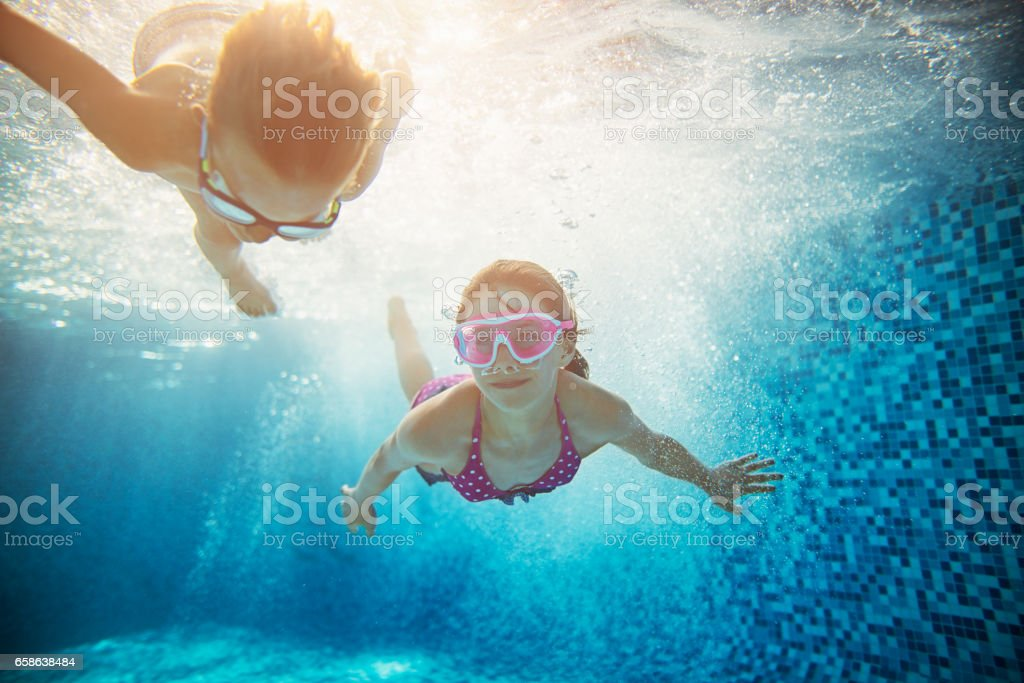 Brother and sister swimming underwater stock photo
