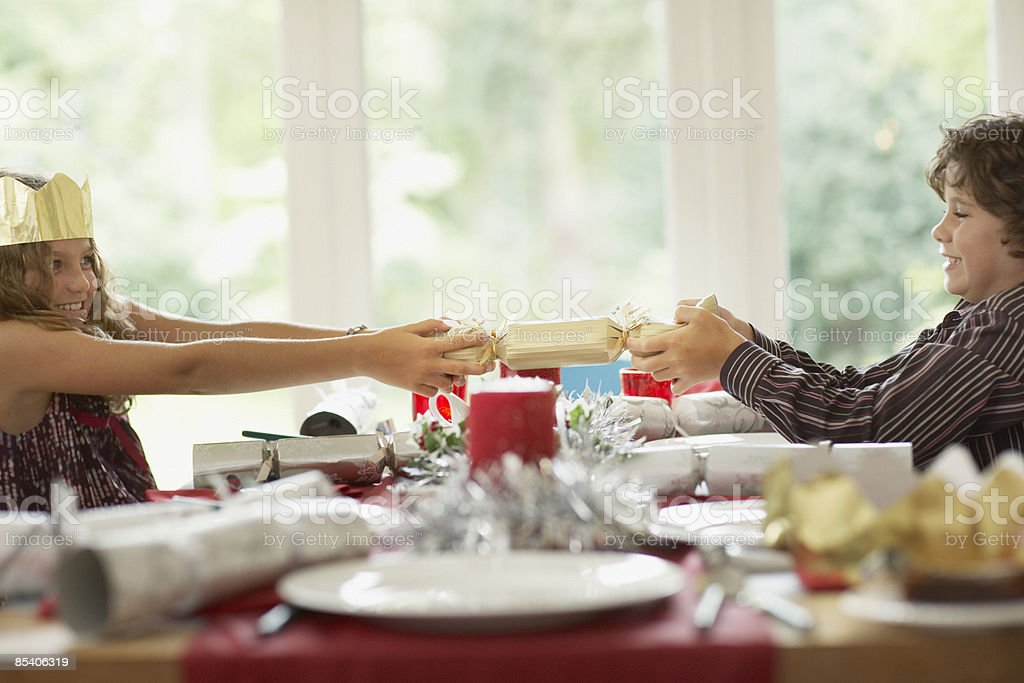 Brother and sister tugging Christmas cracker stock photo