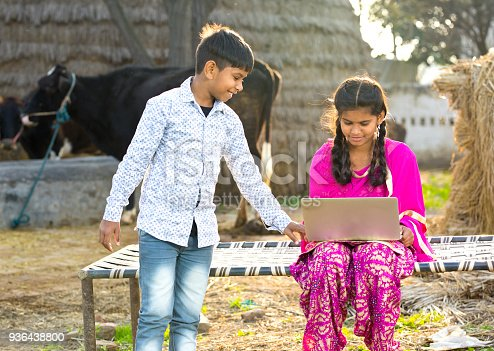 Brother and sister using laptop on traditional bed in village