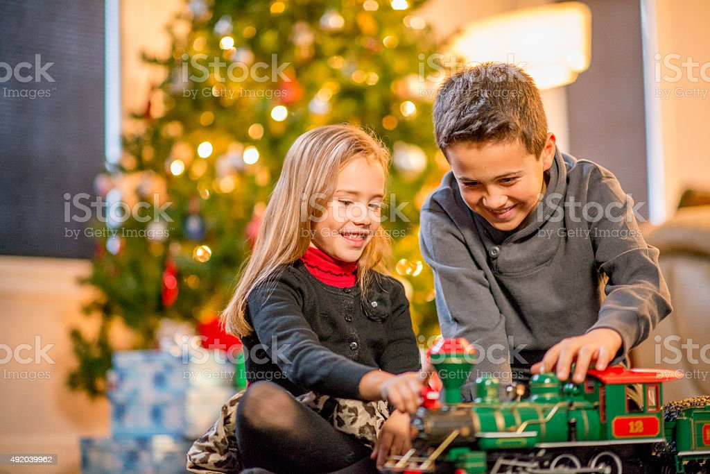 Brother and Sister Watching a Toy Train stock photo