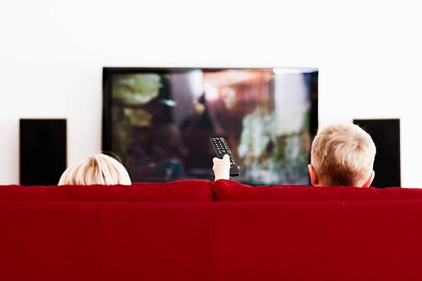 irmão e irmã vê flat screen tv no sofá - tv e familia e ecrã imagens e fotografias de stock