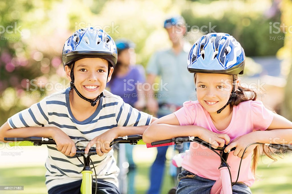 Brother And Sister Wearing Cycling Helmets In Park stock photo