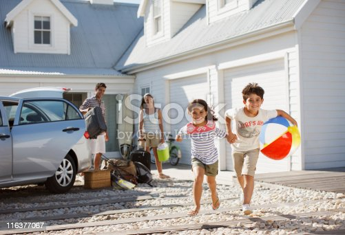 88688880 istock photo Brother and sister with beach ball running on driveway 116377067
