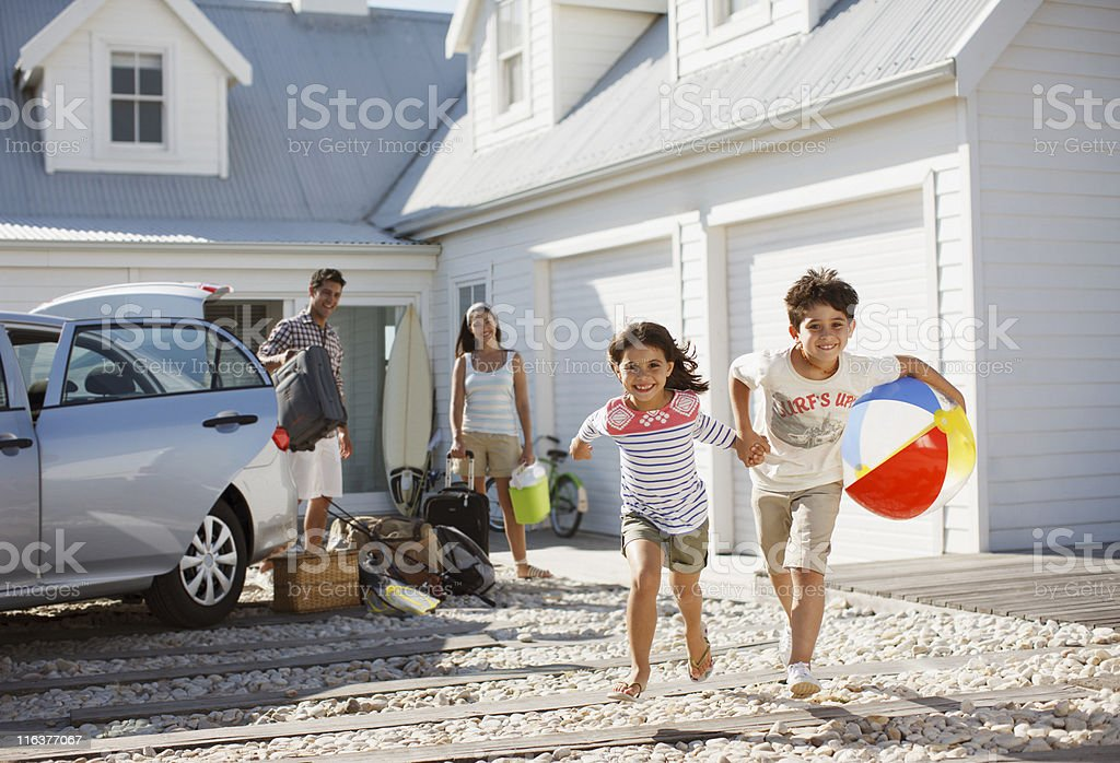 Brother and sister with beach ball running on driveway stock photo
