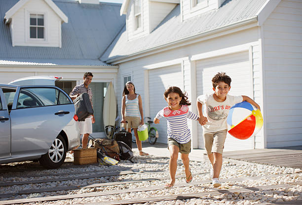 Brother and sister with beach ball running on driveway  holiday villa stock pictures, royalty-free photos & images