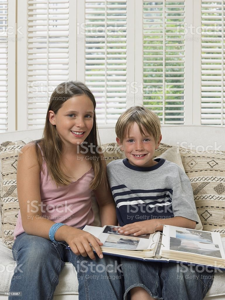 Brother and sister with photo album royalty-free stock photo