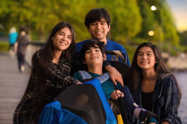 公園で車椅子で障害のある少年を取り巻く兄弟姉妹 - disabilitycollection ストックフォトと画像