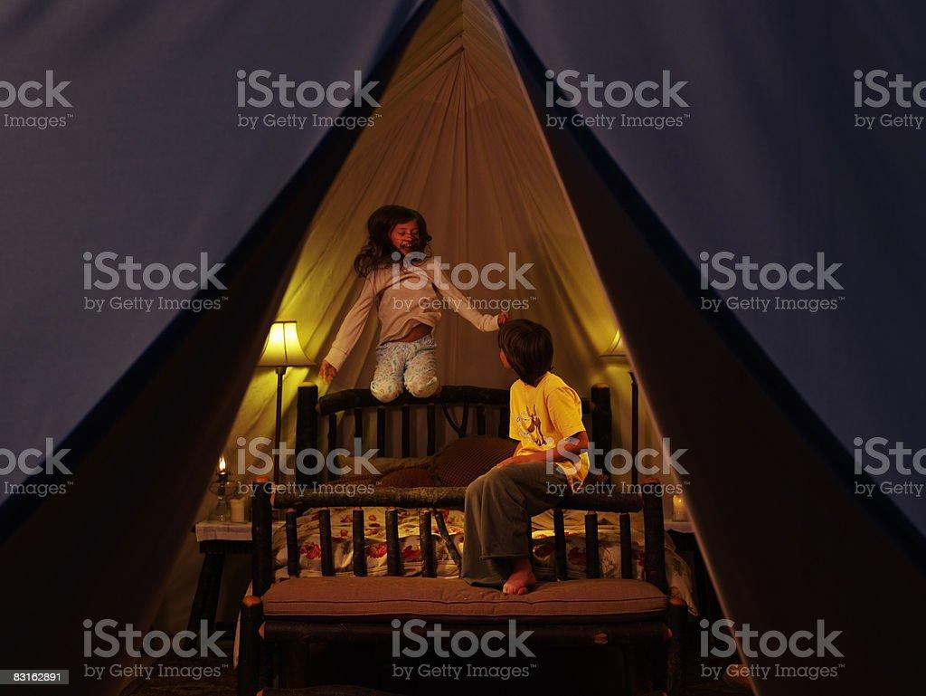 Frère et siter jouant sur lit à l'intérieur de la tente. photo libre de droits
