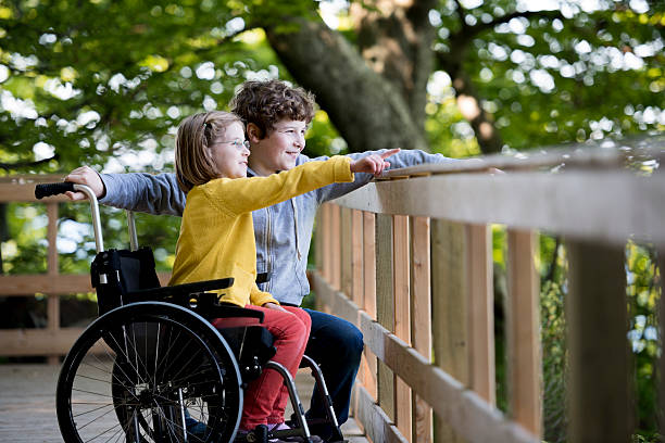 Brother Helping His Disabled Sister Enjoy Her Day Out stock photo