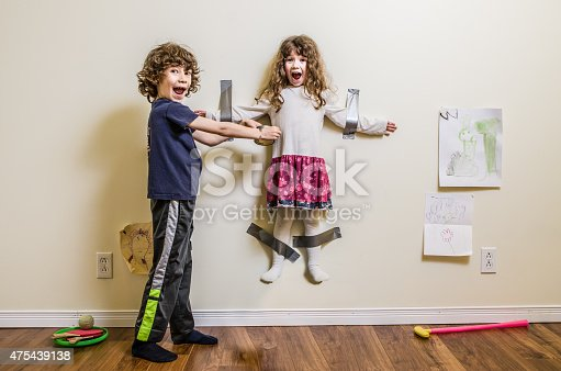 istock Brother hung her sister on the wall 475439138