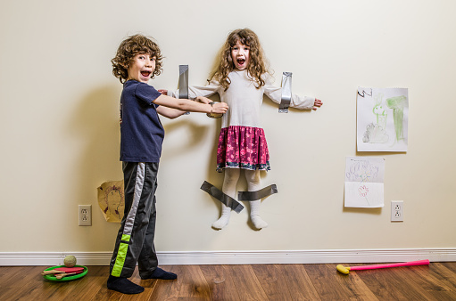 A little boy hung her little sister on the wall using duct tape