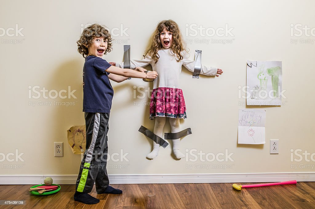 Brother hung her sister on the wall stock photo