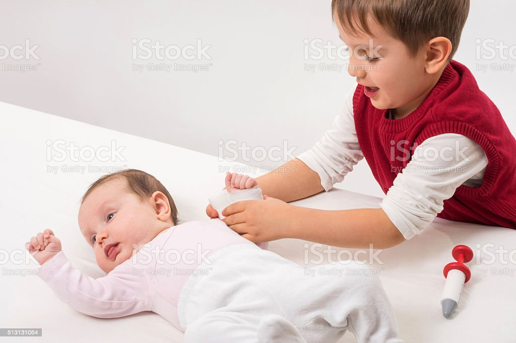 Brother playingwith sister as doctor and patient stock photo