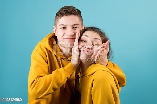 brother squeezes the cheeks of an older sister, fooling around on a blue background. Close-up, teenagers in yellow hoodies