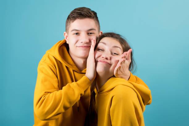 hermano aprieta las mejillas de una hermana mayor, jugando sobre un fondo azul. - foto de stock