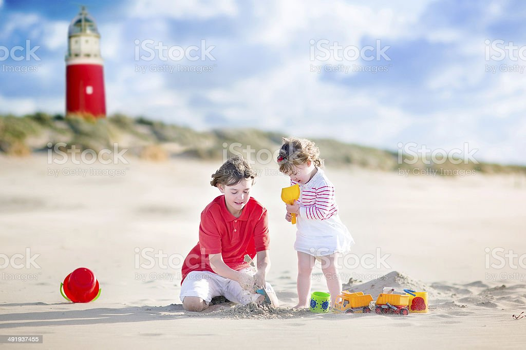 Brother with little sister playing on beach next to lighthouse stock photo