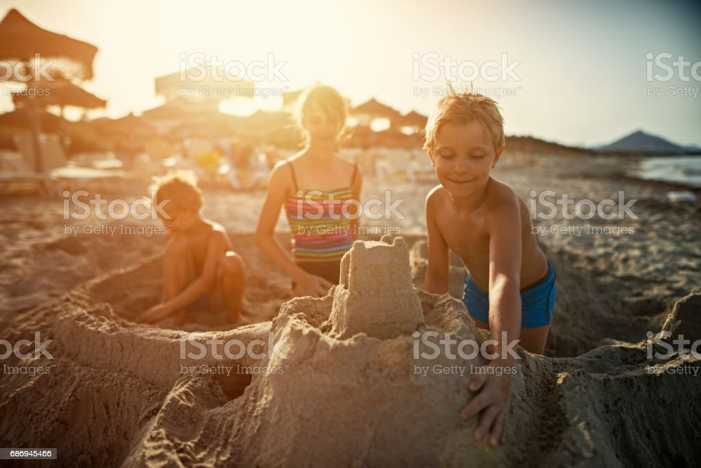 Brothers and sister are building sandcastles on a beach stock photo