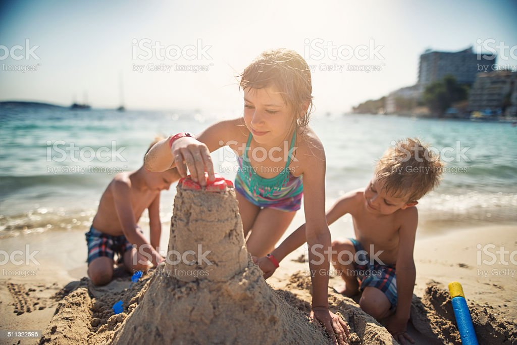 Brothers and sister building a sandcastle on beautiful beach stock photo