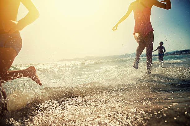 Brothers and sister running on beach on sunset - foto stock