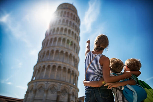 Brothers and sister sightseeing in Pisa Tourists kids sightseeing Pisa, Italy. Brothers and sister are standing in the Piazza del Miracoli amd admiring the famous leaning tower of Pisa.   pisa stock pictures, royalty-free photos & images