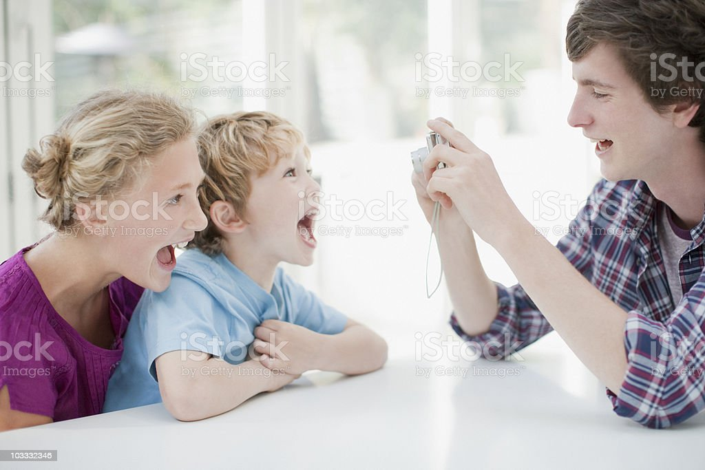 Brothers and sister taking photograph with digital camera royalty-free stock photo