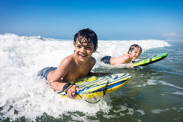 Brothers enjoying the surf on vacation stock photo
